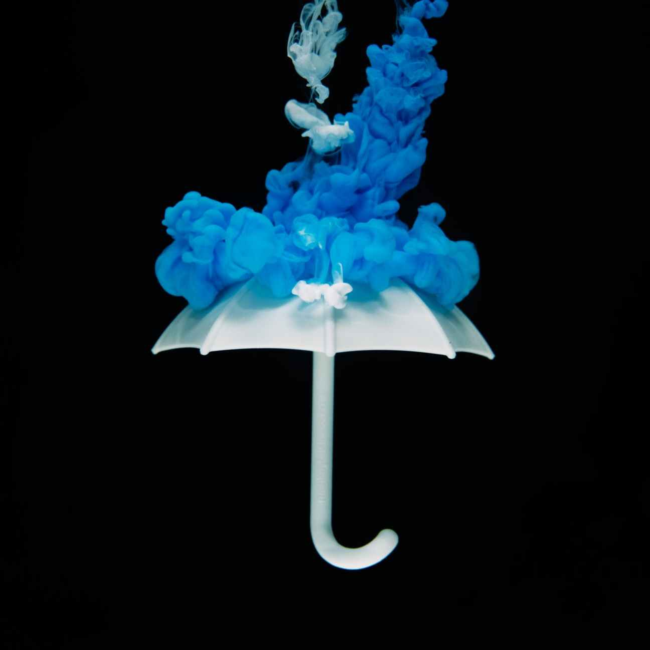 photo of white umbrella with blue smoke illustration