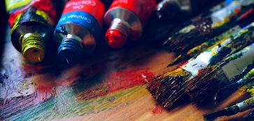 Open oil paint tubes in yellow, red, and blue, with used paintbrushes